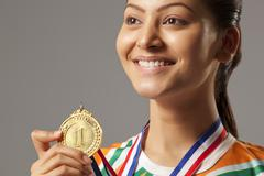 Close-up of young woman holding gold medal isolated over gray background Stock Photos
