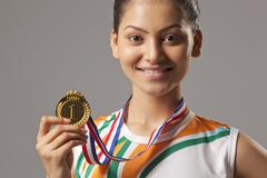 Portrait of young woman holding gold medal isolated over gray background Stock Photos