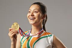 Excited woman holding gold medal isolated over gray background Stock Photos