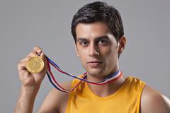 Close-up portrait of young man holding gold medal isolated over gray background Stock Photos