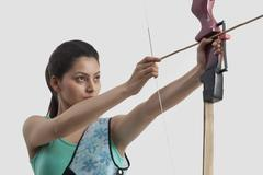 Concentrated woman practicing archery against gray background Stock Photos