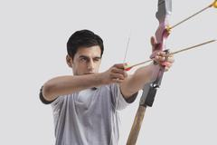 Male archer aiming bow and arrow against gray background Stock Photos