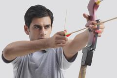 Male archer taking aim with competition bow against gray background Stock Photos