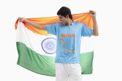 Happy Indian hockey player with Indian flag isolated over white background Stock Photos