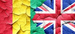 Guinea flag with Great Britain flag on a grunge cracked wall Stock Illustration