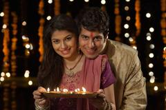 Portrait of a couple with a tray of diyas Stock Photos
