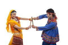 Side view of happy couple performing Dandiya Raas against white background Stock Photos