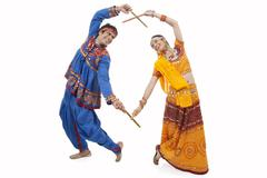 An Indian couple in traditional wear performing Dandiya Raas over white Stock Photos