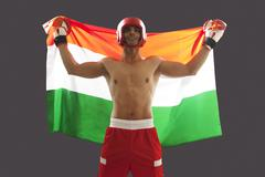 Happy Indian male boxer with national flag standing against gray background Stock Photos