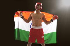 Happy Indian male boxer with national flag standing against black background Stock Photos