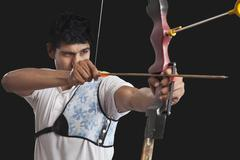 Young man aiming bow and arrow isolated over black background Stock Photos