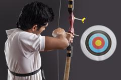 Young man aiming target with bow against black background Stock Photos