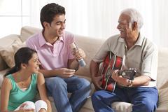 Grandfather playing the guitar and grandchildren singing Kuvituskuvat