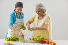 Grandmother and granddaughter working in the kitchen Stock Photos