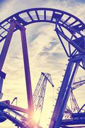 Vintage toned cranes behind roller coaster rails at sunset - stock photo