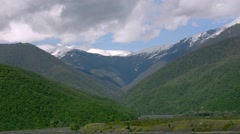The green slopes of the mountains, snow-capped peaks, dark river flowing below. - stock footage