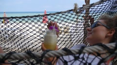 Woman Drinkig Fresh Smoothie on Beach in Hammock Stock Footage