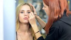 Make-up artist applying eyelash makeup to model's eye. Close up view. Stock Footage