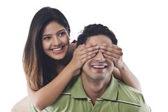 Woman covering mans eyes with her hands Stock Photos