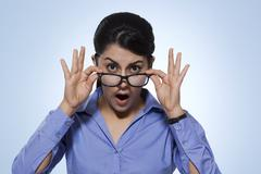 Portrait of amazed businesswoman looking over glasses against blue background Stock Photos
