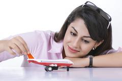 Businesswoman holding toy aeroplane at desk against white background Stock Photos