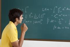 College student trying to solve a maths equation Stock Photos