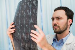 Portrait of a handsome caucasian male radiologist holding x-ray while sitting at Stock Photos