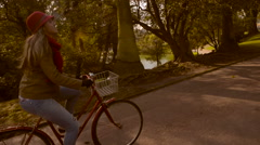 Girl riding bike at the park on fall steady cam Stock Footage