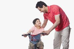 Father assisting son in riding bicycle over white background Stock Photos