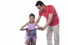 Father assisting daughter in riding bicycle over white background Stock Photos