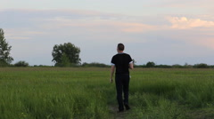 Man walks through the meadow ahead Stock Footage