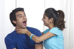 Playful young woman gripping man's neck at home Stock Photos