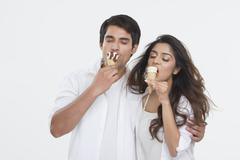 Young couple enjoying ice-cream cones over white background Stock Photos