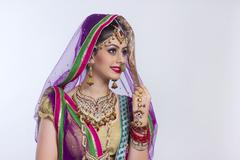 Beautiful Indian bride looking away against gray background Stock Photos