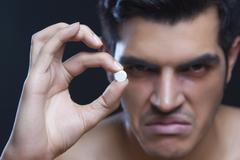 Portrait of angry male drug addict holding pill against black background Stock Photos