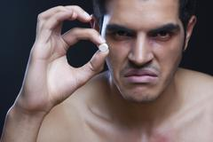 Portrait of angry drug addict holding pill against black background Stock Photos