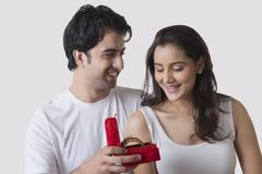 Happy man gifting bangles to woman against white background Stock Photos