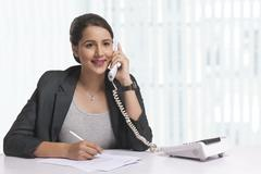 Smiling businesswoman answering telephone at office desk Stock Photos