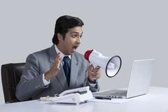 Aggressive businessman shouting through megaphone over laptop at desk against Stock Photos