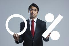 Portrait of disappointed businessman holding zero percentage sign over gray Stock Photos