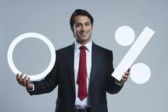 Portrait of happy businessman holding zero percentage sign against gray Stock Photos