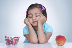 Girl choosing between sweet food and apple against blue background Stock Photos