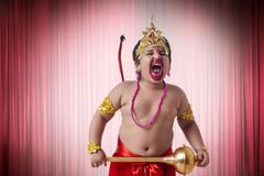 Boy dressed as God Hanuman screaming against red theater curtain Stock Photos