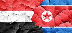 Yemen flag with North Korea flag on a grunge cracked wall Stock Illustration