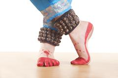 Traditional dancer's feet performing Bharatanatyam against white background Stock Photos