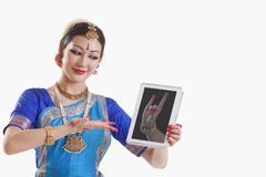 Bharatanatyam dancer showing Simhamukha mudra on digital tablet over white Stock Photos