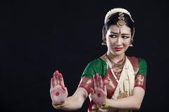 Beautiful woman performing Bharatanatyam on black background Stock Photos