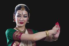 Portrait of young woman making Bharatanatyam gesture called Shankha on black Stock Photos