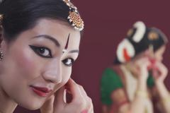 Close-up portrait of Bharatanatyam dancer getting dressed in front of mirror Stock Photos