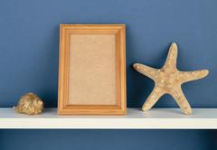 photoframe with starfish on white  shelf on blue wallpaper - stock photo